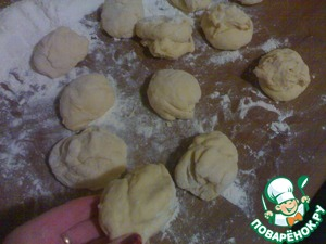 The dough is ready to pass on flour-covered table (I had 1 Cup) to make a sausage and divide into 12 equal parts.  From each part make flat round balls, lay them on a greased baking sheet and cover with a towel to increase two to three times.