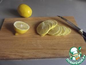 Лимон порезать колечками или полукольцами и поместить его в банку соответствующего размера.