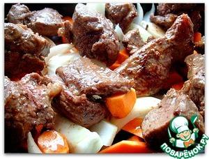 Смазываем маслом форму, в которой будем запекать мясо и овощи. Вниз кладем морковь, тыкву и лук, на них размещаем обжаренную телятину. Поливаем все соком, выделившимся при обжаривании. Отправляем мясо в горячую духовку на 30 минут.