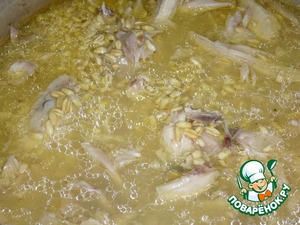 В бульон, где варилась курица, выложить замоченную пшеницу, мясо курицы, посолить, перемешать, поставить казан на рассекатель на небольшой огонь, плотно накрыть крышкой.