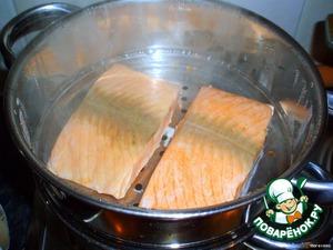 Разрезаем салмон на 2 части и ставим в 1-й ряд парной кастрюльки. Поливаем соком половинки лимона, солим и перчим по вкусу.