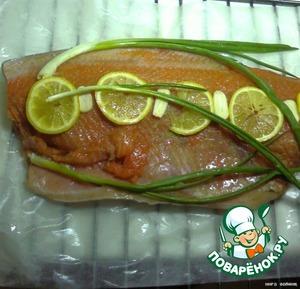 Намочить бумагу для выпечки - на нее уложить филе форели. Посолить, поперчить, сверху положить кружочки лимончика, зеленый лук.