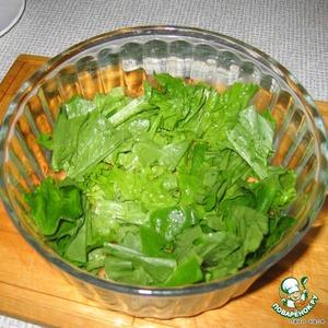 На дно глубокой салатницы руками порвать салатные листья, устроить