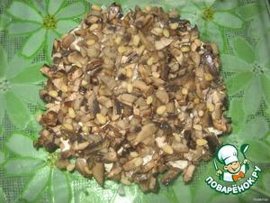 Шампиньоны нарезать и обжарить. Остудить и выложить вторым слоем, посыпать орешками.