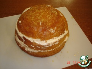 The cooled cake cut into 2 parts and greased with cream