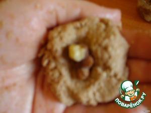 Разделите тесто на кусочки, скатайте шарики, а внутрь вставьте орех. Обмакните в кокосе.