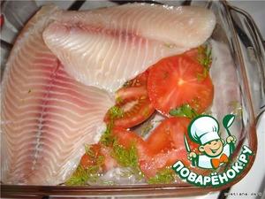 На дно формы укладываем тонко нарезанный помидор.   На него кладем куски рыбы