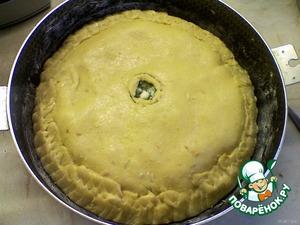 Из маленькой части теста раскатать лепёшку и положить её сверху на начинку.   Края нижнего теста и верхнего защипнуть.   Посередине курника ножом вырезать круг (диаметром 2 см).