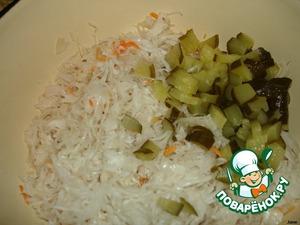 Квашеную капусту выложить в глубокую посуду.    Огурец нарезать кубиками, добавить к квашеной капусте.