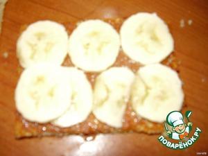 Большой кекс смажьте кремом или сгущенкой, при желании выложите слой фруктов (у нас бананы) и положите еще один кекс.