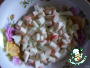В вазу укладываем  слоями   - нарезанные кубиками половину яиц,    - половину крабовых палочек   - половину натертого сыра.