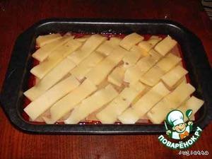 Сыр нарезать тонкими пластинами, равномерно выложить их на поверхности лазаньи.