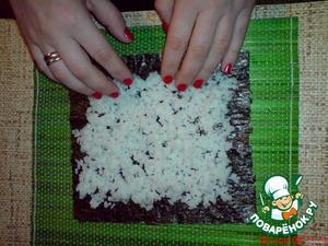 Сверху выложите на него остывший рис, оставляя края для загиба.