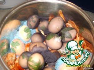 В кастрюлю положить половину луковой шелухи, насыпать 2 ст. л. соли и сверху положить яйца в чулке