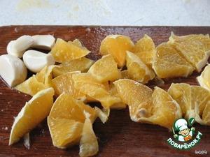Оставшуюся половину апельсина очистить от кожи и порезать маленькими кусочками, выложить в блендер. Добавить чеснок, оливковое масло, соль и измельчить до однородной консистенции.