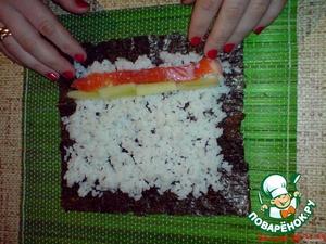 Выложите сверху риса начинку, в моем случае это ломтики форели (я рыбу делала сама, очистила ее от костей, нарезала длинными дольками и слегка просалила).