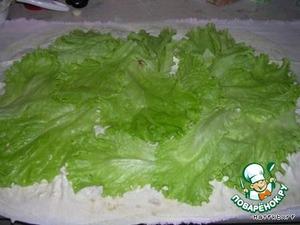 По всей поверхности лаваша раскладываем листья салата (вымытые и высушенные).