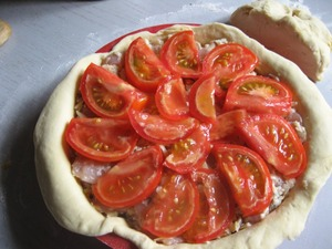 Cut tomatoes into slices and lay on top, wrap edges of the dough inside and cover all with a lid