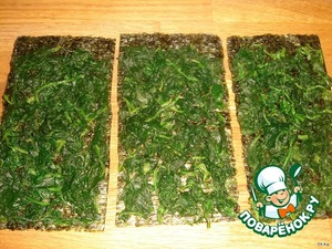 The sheets of nori, gently spread an even layer of the spinach as possible while spreading out the leaves to make a layer of spinach was smooth and thin.  Leave 1-1,5 cm from the top edge, then it is easy to fix the edges.