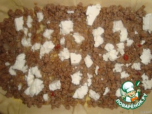 Баклажаны почистить и мелко порезать кубиками, обжарить на оливковом масле до мягкости.На другой сковороде обжарить в оливковом масле раздавленный чеснок и мелко нарезанный лук. Добавить фарш, размешать, когда фарш побелеет, посолить и поперчить по вкусу.    Минут через 5 добавить томатный сок, потушить минут 10.     Готовый фарш смешать с порезанными вялеными томатами, петрушкой, твердым сыром и баклажанами.   Выложить начинку на тесто.    Яйца взбить и залить начинку.    Сверху раскрошить фету.