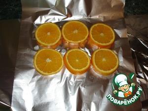 Фольгу уложить на противень. Выложить дольки апельсина на фольгу.