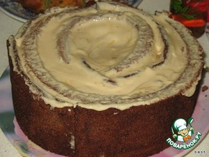 Остальные полоски промазываем кремом и располагаем вокруг центрального рулета, прижимая каждый слой к предыдущему.   Собрав весь торт, подравниваем его края и ставим на ночь в холодильник.