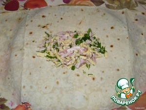 Lavash is divided into two parts. On a pita spread the filling and wrap.  Wrap - step 1.
