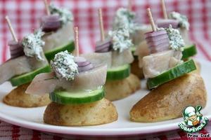 Собрать канапе - на картофель выложить огурец, сельдь, лук, закрепить шпажкой. Сверху добавить шарик творожной смеси.