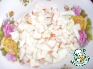 Трем немного замороженного сливочного масла и повторяем все слои снова:   - нарезанные кубиками половину яиц,    - половину крабовых палочек   - половину натертого сыра.    Смазываем майонезом   В центр кладем оставшуюся жемчужину.