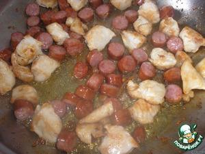 В большой и глубокой сковороде 5 минут обжариваем курицу. Затем к ней отправляем колбаски и жарим еще 3 минуты.