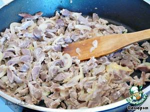 Лук нарезаем полукольцами и обжариваем вместе с желудочками на растительном масле до золотистости.