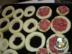 Spread on a baking sheet, greased with vegetable oil, the slices of zucchini. Fill the middle of the meat.