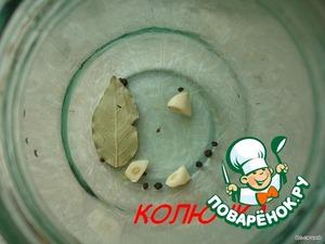 In a jar put zubochka garlic, Bay leaf and pepper