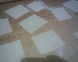Тесто разморозить, раскатать и разрезать на квадраты.