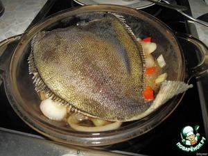 Перекладываем овощи на сковородку, сверху укладываем рыбку, слегка перчим и посыпаем базиликом. Готовим под крышкой на среднем огне 7-10 минут, перевернув камбалу один раз.