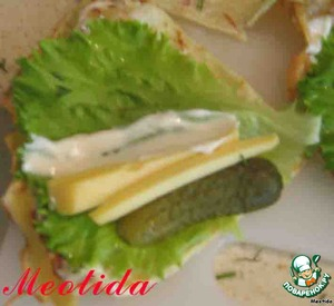 on a leaf of lettuce with one hand, spread half a cornichon and a block of cheese, a little mayonnaise or creamy mustard dressing