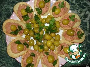В середину тарелки выложить горку из оливок. Украсить зеленью.