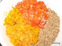 3. Выложить фарш в миску, на этой же сковороде обжарить морковку, натертую на терке, и лук, добавить в фаршу. Помидоры очистить от кожицы, порезать, половину положить в фарш. Перемешать. Добавить рис.