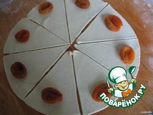 Тесто достать из холодильника, раскатать в тонкий пласт, вырезать большой круг и разрезать круг на сегменты. На каждый сегмент положить по 1 шт. кураги и закатать, начиная с широкой стороны
