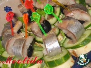 шпажкой прикрепляем ломтик селедки и оливку