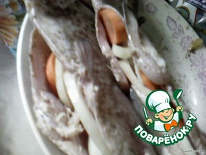 Вовнутрь рыбы положить кольца лука и кружочки моркови, лавровый лист.