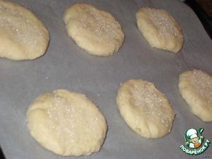 И расплющить шарик на ладони примерно до 2 см толщиной, выложить на противень.   Каждую лепешку посыпать сахаром и слегка вдавить его, расплющив при этом лепёшку до 1,5 см толщины.   Выпекать примерно 12-15 минут, в зависимости от диаметра и толщины. Сметанники должны слегка подрумяниться с краев, в серединке оставаясь белыми и слегка мягкими.   Аккуратно переложить на решетку и, пока горячие, посыпать смесью сахарной пудры с ванилином.   Дать остыть.