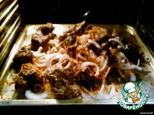 Когда мясо подрумянится, добавить к нему натертую морковку и лук полукольцами. Все вместе опять прижарить.