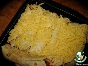 Укладываем наши бурритос в смазанную растительным маслом форму и посыпаем тертым твердым сыром. Пару штук у меня без сыра, так как в нашей семье не все его употребляют.