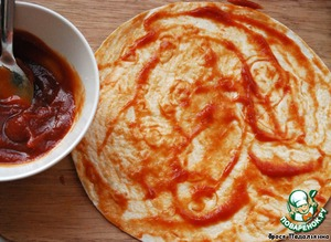 Смешать кетчуп и соус чили, смазать смесью каждую лепешку.    Если берете томатную пасту, разбавьте ее чуть-чуть водой.