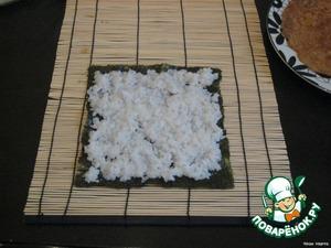 Берем циновку, на нее кладем лист нори. Сверху распределяем рис (уже остывший).