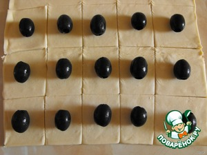 Thaw the dough, unwrap and cut squares of about 5 cm.  On each square put some of the olives.