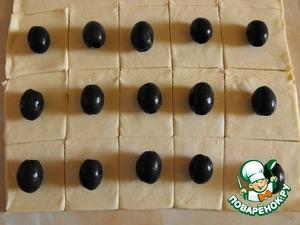 Разморозить тесто, развернуть и нарезать квадратиками примерно по 5 см.   На каждый квадрат выложить оливку.