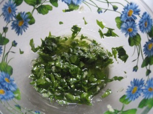 Prepare the marinade. Parsley finely chop, garlic squeeze through the press, add the olive oil.