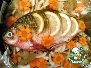 Из оставшегося лимона выжать сок и полить им рыбу.   Запекать 30-40 минут до готовности. Выложить рыбу на листья салата, украсить зеленью.
